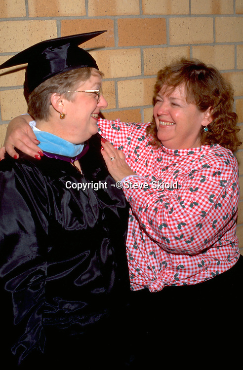 Friends age 56 celebrating masters degree graduation at St Thomas University  St Paul  Minnesota USA