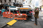 People pass an area cordoned off for a large crane to operate in central London, England, United Kingdom.