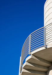Detail of a concrete building and staircase against a cloudless blue sky