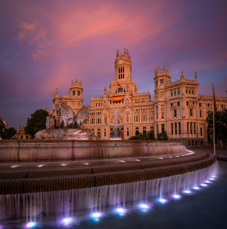 "The Plaza de Cibeles is a square with a neo-classical complex of marble sculptures with fountains that has become an iconic symbol for the city of Madrid. It sits at the intersection of Calle de Alcalá (running from east to west), Paseo de Recoletos (to the North) and Paseo del Prado (to the south). Plaza de Cibeles was originally named Plaza de Madrid, but in 1900, the City Council named it Plaza de Castelar, which was eventually replaced by its current name.<br /> <br /> It is currently delimited by four prominent buildings: the Bank of Spain Building, the Palacio de Buenavista, the Palace of Linares (""Palacio de Linares""), and the Cybele Palace (""Palacio de Cibeles""). These constructions are located in four different neighbourhoods from three different adjacent districts: Centro, Retiro, and Salamanca.<br /> <br /> Over the years, Cybele Palace and her fountain have become symbolic monuments of the city. The fountain of Cybele is found in the part of Madrid commonly called the Paseo de Recoletos. This fountain is named after Cybele, a Phrygian goddess. The fountain is traditionally the place where Real Madrid C.F. celebrate their team victories, with the team captain placing a Real Madrid flag and scarf on the statue.["