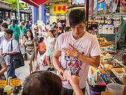 """23 DECEMBER 2012 - SINGAPORE, SINGAPORE:  A juice seller accepts payment from a customer in the New Bugis Street market. New Bugis Street is billed as """"the largest street-shopping location in Singapore"""". Although the street is not a well-known tourist destination, it is frequented by many Singaporeans.  PHOTO BY JACK KURTZ"""
