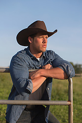 portrait of a very good looking All American Cowboy leaning on a fence outdoors on a ranch