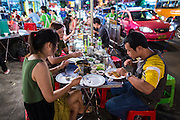 11 SEPTEMBER 2013 - BANGKOK, THAILAND:  People eat at T and K Seafood stand in the Chinatown section of Bangkok. T and K Seafood was one of the first street stall restaurants in Bangkok and is more of a pop up restaurant than a street food stall. It has sit down service and full menus, but seating is on the street and sidewalk and food is prepared in portable cookers that are brought out to the street when the restaurant opens. Thailand in general, and Bangkok in particular, has a vibrant tradition of street food and eating on the run. In recent years, Bangkok's street food has become something of an international landmark and is being written about in glossy travel magazines and in the pages of the New York Times.        PHOTO BY JACK KURTZ