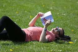 © Licensed to London News Pictures. 04/05/2016. Leeds, UK. A man reads a book in the bright warm sunshine in Hyde Park in Leeds, West Yorkshire. Britain is experience warmer weather this week with temperatures to rise to 23 degrees celsius this weekend. Photo credit : Ian Hinchliffe/LNP