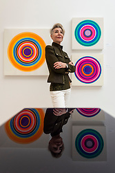 """© Licensed to London News Pictures. 14/10/2021. LONDON, UK. Artist Fara Thomas poses with her resin works (L) """"Tangerine Sun"""", and (R) """"Merry Go Round"""" and """"Vortex"""". Opening day of the eighth edition of START, an art fair presenting contemporary works by over 70 emerging international artists and galleries from over 25 countries.  The show runs to 17 October at Saatchi Gallery in Chelsea.  Photo credit: Stephen Chung/LNP"""