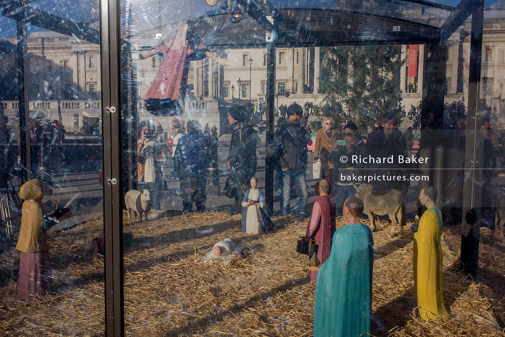 A holy nativity scene titled Christmas Crib by the artist Tomoaki Suzuki with background tourists in London's Trafalgar Square.