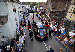© Licensed to London News Pictures. 10/07/2020. Ditchling, UK. The funeral cortege carrying the body of WWII Forces' Sweetheart Dame Vera Lynn passes through her home village  Ditchling, East Sussex followed on foot by her daughter Virginia Lewis-Jones and husband Tom. The cortege will head to a crematorium in Brighton for a private funeral. A Battle of Britain Memorial Flight flypast, consisting of a Spitfire and a Hurricane, will perform a flypast at noon. Photo credit: Peter Macdiarmid/LNP
