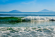 Waves and curls coming into An Bang Beach during the day. Emerald Green wave with Cham Island in far off distance.
