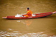 "10 JULY 2011 - AMPHAWA, SAMUT SONGKRAM, THAILAND:   A Buddhist monk from Wat Amphawan Chetiyaram in Amphawa, Thailand, about 90 minutes south of Bangkok, paddles down the main canal during his alms round. Most of the monks from the temple use boats to go from house to house on their alms rounds. The Thai countryside south of Bangkok is crisscrossed with canals, some large enough to accommodate small commercial boats and small barges, some barely large enough for a small canoe. People who live near the canals use them for everything from domestic water to transportation and fishing. Some, like the canals in Amphawa and nearby Damnoensaduak (also spelled Damnoen Saduak) are also relatively famous for their ""floating markets"" where vendors set up their canoes and boats as floating shops.      PHOTO BY JACK KURTZ"