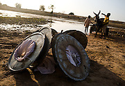 Mesh filters use to prevent guinea worm lay on the ground while two boys drive the donkey-pulled cart they use to carry large barrels of water at the Dikunani dam in Savelugu, northern Ghana, on Friday March 9, 2007. The only of four water sources that has not completely dried out around Savelugu, the pond is used by hundreds of people daily who sometimes walk several kilometers to fetch water. Despite the presence of mesh filters available to people who come get water, cases of guinea worm in the area have gone up sharply in the recent months.