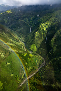 """From a helicopter, see a rainbow and Manawaiopuna Falls (aka """"Jurassic Falls"""") in Hanapepe Valley, which was spectacularly featured as the helipad location in the 1993 film """"Jurassic Park."""" Located on private land, the falls are best visited via helicopter tour over the island of Kauai, in the state of Hawaii, USA."""