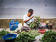 27 OCTOBER 2015 - YANGON, MYANMAR: A woman sells basil and herbs in the market at Aungmingalar Jetty in Yangon. The market is home to one of the largest fish markets in Yangon and a meat and produce market.    PHOTO BY JACK KURTZ