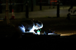 © Licensed to London News Pictures. 15/08/2021. Slough, UK. A forensic investigator gathers evidence at the scene following a double stabbing in Cippenham, Slough. Emergency services were called at approximately 17:00BST on Sunday 15/08/2021 to the Eltham Avenue area of Slough to reports that two male teenagers had been assaulted during an altercation between a number of youths. Both were taken to hospital with stab wounds. Photo credit: Peter Manning/LNP