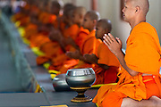 """22 JULY 2013 - PHRA PHUTTHABAT, THAILAND:   A senior monk leads novices in a chanting service during the Tak Bat Dok Mai at Wat Phra Phutthabat in Saraburi province of Thailand, Monday, July 22. Wat Phra Phutthabat is famous for the way it marks the beginning of Vassa, the three-month annual retreat observed by Theravada monks and nuns. The temple is highly revered in Thailand because it houses a footstep of the Buddha. On the first day of Vassa (or Buddhist Lent) people come to the temple to """"make merit"""" and present the monks there with dancing lady ginger flowers, which only bloom in the weeks leading up Vassa. They also present monks with candles and wash their feet. During Vassa, monks and nuns remain inside monasteries and temple grounds, devoting their time to intensive meditation and study. Laypeople support the monastic sangha by bringing food, candles and other offerings to temples. Laypeople also often observe Vassa by giving up something, such as smoking or eating meat. For this reason, westerners sometimes call Vassa the """"Buddhist Lent.""""   PHOTO BY JACK KURTZ"""
