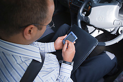 Social worker making notes on electronic device in car.