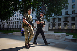 © Licensed to London News Pictures. 25/05/2017. London, UK. An Armed soldier and police officer patrol Westminster, London following a terrorist attack in Manchester, northern England, earlier this week. 23 people were killed an dozens more injured when Salman Abedi set off a suicide bomb at an Ariana Grande concert.  Photo credit: Ben Cawthra/LNP
