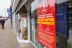 © Licensed to London News Pictures. 01/04/2020. PINNER, UK.  A sign in the window of a pharmacy in the high street in historic Pinner, north west London, informs passers-by not to enter if the individual is thought to have coronavirus (COVID-19) symptoms.  The UK is entering its second week of lockdown and 1,789 deaths as a result of COVID-19 have been reported.  Photo credit: Stephen Chung/LNP