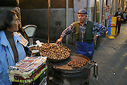 A woman sells lottery tickets near a vendor offering hot roasted chestnuts for 1 euro, Rome, Italy. (Supporting image from the project Hungry Planet: What the World Eats.)