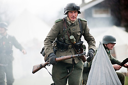 Reeactor portraying Panzer Grenadier from the 21st Panzer division carrying a Mauser K98 rifle with a Stick Grenade (Steilhandgranate) tucked into his belt.21 April  2013.Image © Paul David Drabble