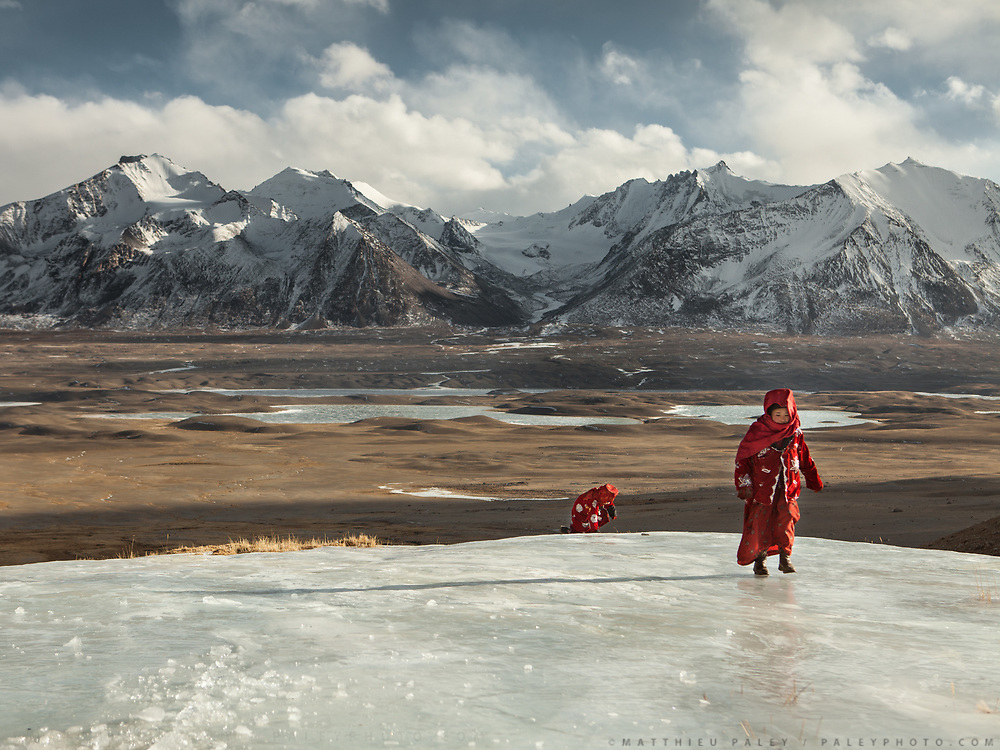 Two young Kyrgyz girls fetching water in winter - they need to break the ice to get to the spring.<br /> Ech Keli, Er Ali Boi's camp, one of the richest Kyrgyz in the Little Pamir.