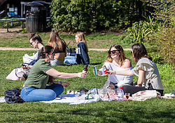 © Licensed to London News Pictures. 29/03/2021. London, UK. From left, Liana Winzer, 28, Milly Clogg, 26 and Luka Vala, 27 enjoy a picnic in the sunshine along the River Thames at Richmond, South West London as weather forecasters predict highs of 23c in London and the South East. From today, Monday 29 March, two households or six people will be allowed to meet up marking the end of the Stay at Home advice. Playing golf, tennis and organised outdoor sports will also be allowed as England starts to unlock after a year of Covid-19 restrictions. Photo credit: Alex Lentati/LNP