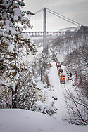 During a break in the snow squals, a northbound ethanol train with run through power passes under the Bear Mountain Bridge and is about to enter the Fort Montgomery tunnel.