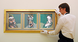 © Licensed to London News Pictures. 07/10/2011. LONDON. UK. A Sotheby's worker holds Three Studies for a self Portrait by Francis Bacon.  at Sotheby's Preview.  The piece will be sold at auction in October 2011 and is expected to fetch $15/20million. Photo credit:  Stephen Simpson/LNP