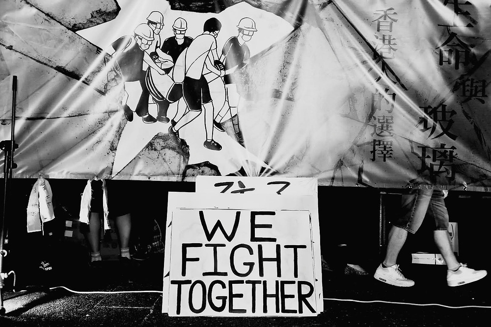 """A sign reads, """"We Fight Together"""" amongst protesters' feet during the June protests in Hong Kong. Protesters are opposed to a controversial extradition bill."""