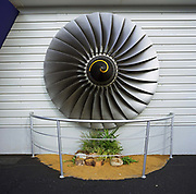 A Rolls-Royce turbofan has been fixed to the exterior of the company's sales stand at the Farnborough Air Show in Hampshire, England. The British-owned company have been making aircraft engines since 1914 at the start of the First World War, in response to the nation's needs, Royce designed his first aero engine – the Eagle. Modern airliners have the Trent engine's technology embedded in its power plants and Farnborough is a major showcase for its many designs. Here, their chalet has a mocked-up garden feature complete railings and the turbine blades attached to the wall above. Picture from the 'Plane Pictures' project, a celebration of aviation aesthetics and flying culture, 100 years after the Wright brothers first 12 seconds/120 feet powered flight at Kitty Hawk,1903.