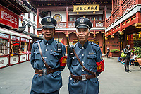Shanghai, China - April 7, 2013: two tourist policemen posing and smiling in Fang Bang Zhong Lu old city at the city of Shanghai in China on april 7th, 2013