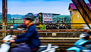 Fine Art:<br /> March 2017. Hanoi: In motion blurr of motorcycle riders on the red river bridge with a fruit stand in the far background.<br /> <br /> Long Biên Bridge is the bridge that runs across the Red River. This bridge connects Long Bien district to Hoam Kiem district in Hanoi. It is a famous bridge because it was never totally destroyed in the American/Vietnam war in the 60's and 70's. RAW to Jpg