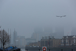 © Licensed to London News Pictures. 18/12/2016. LONDON, UK.  Canary Wharf skyscrapers are shrouded in fog, seen across the River Thames this morning. Foggy weather continues to disrupt flights from London airports this morning.  Photo credit: Vickie Flores/LNP