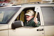 02 APRIL 2006 - THREE POINTS, AZ: Bruce McDoniel holds up his placard indicating that he is assigned to Observation Post 1 before going out on the Minuteman line between Three Points and Arivaca, Arizona, off Highway 286 Sunday. Volunteers from the Minuteman Project have set up lines of observation posts on remote county roads in the desert southwest of Tucson to monitor the area for illegal immigrant traffic. On Saturday night, the first night of the action, Minuteman volunteers spotted more than 50 illegal immigrants and claim their tips to the US Border Patrol led to the apprehension of at least 16 of those immigrants.  PHOTO BY JACK KURTZ