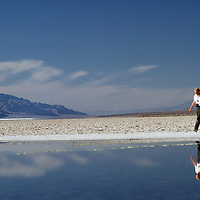 Tourist in California's Death Valley National Park walks by saline pond at Badwater, lowest & hottest point in western hemisphere.