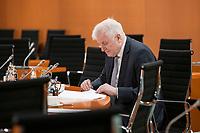 01 APR 2020, BERLIN/GERMANY:<br /> Horst Seehofer, CSU, Bundesinnenminister, liest in seinen Unterlagen, vor Beginn der Kabinettsitzung, die aufgrund der Abstandsregeln anl. der Corona-Pandemie im  Internationalen Konferenzsaal stattfindet, Bundeskanzleramt<br /> IMAGE: 20200401-01-002<br /> KEYWORDS: Kabinett, Sitzung
