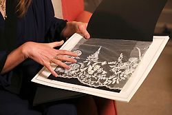 Clare Waight Keller, who designed Meghan Markle's wedding dress, holds a piece of lace during an interview at Kensington Palace in London. Ms Waight Keller, who made history as the first female artistic director at French fashion house Givenchy, was revealed as the designer of the eagerly awaited wedding dress on Saturday morning.