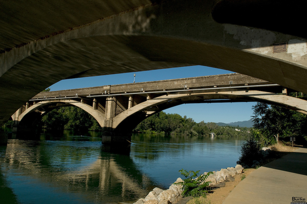 The Diestelhorst Bridge in Redding, California was built in 1914. When completed in 1915, it linked the county seats of Redding and Yreka. Today, it is listed on the National Register of Historic Places...The bridge is 639 feet long and 24.3 feet wide, and has nine spans. It was named for Gotlieb Diestelhorst, whose family owned the land where it was built. Some of the family members even helped build the bridge...The bridge has the distinction of being the first bridge for automobiles and the first reinforced concrete bridge built across the Sacramento River in Northern California.   It is now used as a pedestrian bridge for biking, hiking and other outdoor activities...The Lake Redding Bridge was built in 1997 as a modern update to the older bridge trying to maintain its look and feel. ..The Sacramento River, California's largest river flowing 375 miles, from Mount Shasta in the north through the Central Valley and the Delta to San Francisco Bay, this river constitutes an irreplaceable resource to Northern California's ecology...Boating, fishing, camping and swimming on the Sacramento and its reservoirs attract more than 8 million visitors a year. ..The 21-mile stretch from Redding to Balls Ferry is perfect for scenic touring and shorter trips. For the adventuresome, the breath-taking 33-mile stretch between Balls Ferry and Red Bluff is your ticket...The Sundial Bridge is actually a working Sundial is 700 feet long, 23 feet wide and 217 feet high (pylon). The bridge weighs 3.2 million pounds (1,600 tons) and is composed of steel with galvanized steel cables. The deck materials are non-skid glass panels in steel framework with granite accents. The foundation consists of 115 tons of rebar, 1,900 cubic yards of concrete and a superstructure of 400 tons of steel. 200 tons of glass and granite were utilized in deck construction. The bridge contains 4,342 feet of cable and the pylon is 580 tons of steel.