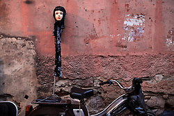 A motorbike and a doll's head are seen inside the souk surrounding Djemaa el Fna square, meaning Place of the Dead, in Marrakech, Morocco on May 13, 2009.
