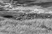 Digitally manipulated image of stones in a field with dramatic sky
