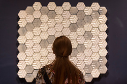 """© Licensed to London News Pictures. 11/09/2018. LONDON, UK. A staff member views upcycled tiles made by """"Trashpresso"""", designed by Miniwiz, a mobile solar-powered recycling plant, at a preview of the 87 nominees for the eleventh Beazley Designs of the Year exhibition and awards at the Design Museum in Kensington.  The exhibition runs 12 September to 6 January 2019 and celebrates the most innovative designs of the last year.  Photo credit: Stephen Chung/LNP"""