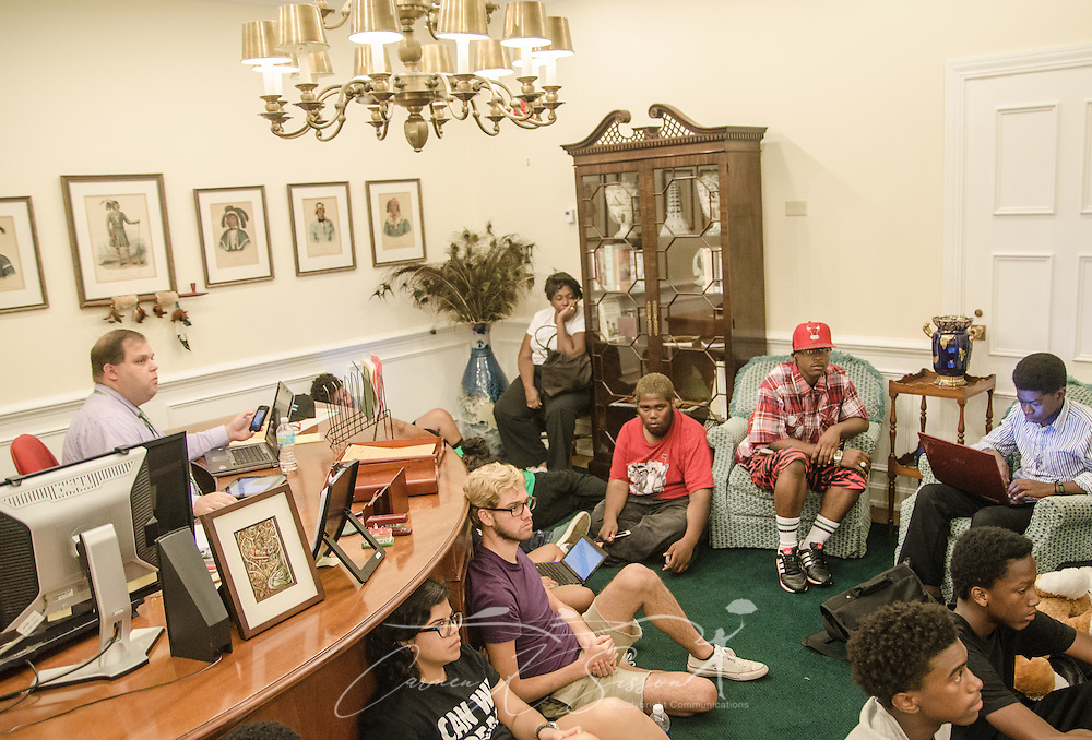 Pat Fargason  (left), communications specialist for the Florida Department of Juvenile Justice, keeps a watchful eye on a Dream Defenders meeting July 23, 2013 in Florida Gov. Rick Scott's office in the state capitol in Tallahassee. Members of the youth-led activist group moved into the capitol July 16, 2013 and have refused to leave until the governor agrees to hold a special legislative session to address issues like racial profiling, the school-to-prison pipeline, and Florida's stand-your-ground law. (Photo by Carmen K. Sisson/Cloudybright)
