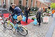 Bij de Vismarkt in Groningen pakt een jonge vrouw haar fiets met boodschappen, net voor het punt waar geen fietsen geplaatst mogen worden.<br /> <br /> Near the Vismarkt in Groningen a young woman is getting her bike with the groceries, just in front of the sign that shows bike parking is not allowed.