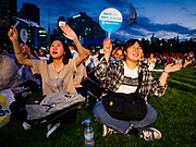 "15 JUNE 2018 - SEOUL, SOUTH KOREA:  Women cheer for patriotic entertainers during a rally to mark the anniversary of the signing of the June 15th North–South Joint Declaration between South Korea and North Korea. The Declaration was negotiated by late South Korean President Kim Dae-jung and North Korean leader Kim Jong-il and signed on 15 June 2000. It was a part of South Korea's ""Sunshine Policy,"" which guides the South's relationship with North Korea. This year's observance of the anniversary was bolstered by the recent thawing in relations between North Korea and South Korea and the US.   PHOTO BY JACK KURTZ"