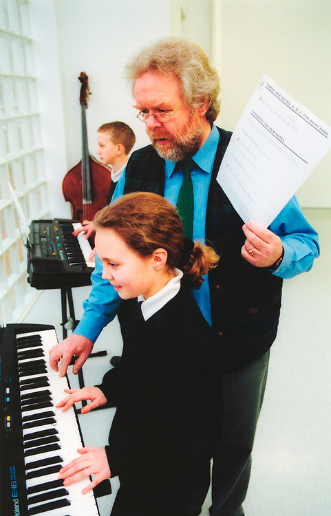 Music teacher and pupils in lesson at secondary school UK