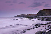 View of Kilve Beach at dusk, with lilac and purple pastels in the sky and water and cliffs in the background.