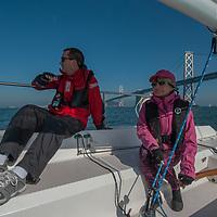 Aa sailboat cruises past the Bay Bridge, spanning San Francisco Bay, California.