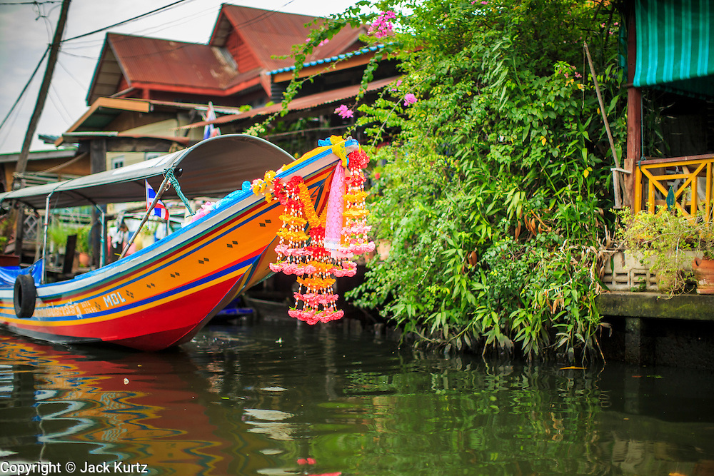 """17 NOVEMBER 2012 - BANGKOK, THAILAND:  A """"long tailed"""" boat in the Thonburi section of Bangkok. Long tailed boats use big V8 car engines and have 30-40 foot long propeller shafts that extend past the back of the boat. Bangkok used to be known as the """"Venice of the East"""" because of the number of waterways the criss crossed the city. Now most of the waterways have been filled in but boats and ships still play an important role in daily life in Bangkok. Thousands of people commute to work daily on the Chao Phraya Express Boats and fast boats that ply Khlong Saen Saeb or use boats to get around on the canals on the Thonburi side of the river. Boats are used to haul commodities through the city to deep water ports for export.    PHOTO BY JACK KURTZ"""