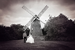 Bride and Groom smiling, walking hand in hand at New Bradwell Windmill