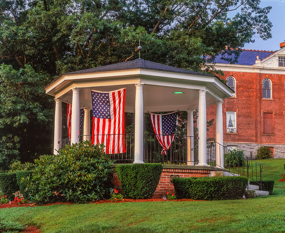 Gazebo with American flags hanging, on village green in summer, brick Town Hall beyond, Watertown, CT