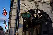The entrance of the arcade outside The Ritz with Union Jack flags and distant architecture on Piccadilly, on 7th February 2018, in London, England.
